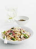 Ribbon noodles with strips of ham, zucchini and red onion