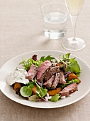 Sliced lamb fillet with mint yogurt on a bed of salad
