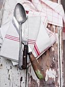 Spoon, two knives and dish towels on a wooden surface