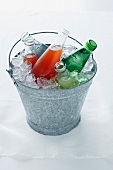Beverage bottles in a pail with ice cubes