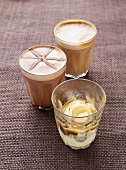 Three coffees with frothy milk in glasses