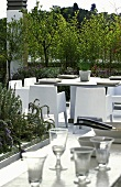A dining table with chairs on a luxuriously planted roof terrace