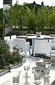 Esstisch mit Stühlen auf üppig bepflanzter Dachterrasse