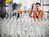 Fabrikarbeiter prüft Glasflasche