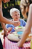 Ältere Frau sitzt beim Picknicktisch