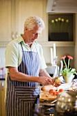 Älterer Mann kocht in der Küche