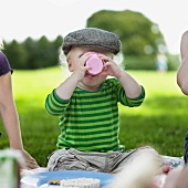 Boy drinking from cup at picnic