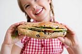 Mädchen hält ein Sandwich