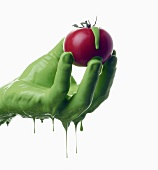 A green-painted hand holding a tomato