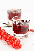 Glasses of redcurrant jelly and fresh redcurrants