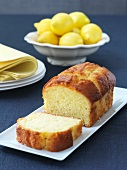 Sliced Loaf of Lemon Pound Cake with a Bowl of Lemons in Background