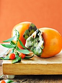 Two Persimmons on a Cutting Board