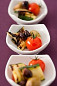 Bowls of antipasti (tomatoes, courgette and olives)