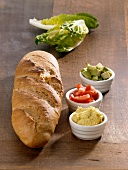 Ingredients for a baguette with an avocado dip (bread, curry dip, tomatoes, avocado and lettuce)