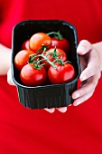 A young woman holding a plastic box of tomatoes