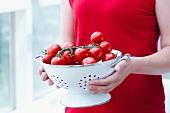 Junge Frau hält Fussseiher mit Tomaten