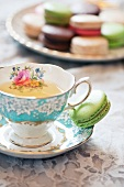 Grüntee in romantischer Tasse mit grüner Makrone