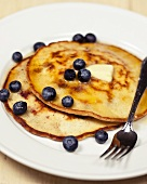 Two Coconut Blueberry Pancakes on a Plate with Melting Butter and a Fork