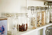 Various dried fruits and cereals in storage jars on a kitchen shelf