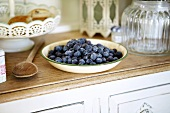 A bowl of blueberries on a kitchen dresser