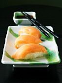 Salmon Sushi with Chopsticks and a Bowl of Soy Sauce