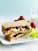 Peanut Butter and Jelly Sandwich on Wheat Bread with Celery and Grapes