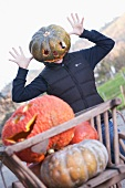 Person wearing a hollow pumpkin on their head