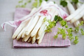 A bunch of white asparagus with a decorative ribbon and lady's mantle