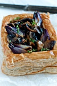 A puff pastry tart with mushrooms and red onions