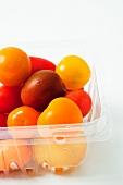 Various coloured tomatoes in a plastic container