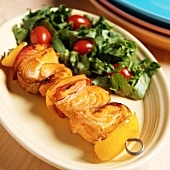 Salmon Kabob Red and Yellow Bell Peppers on a Metal Skewer; Side Salad