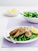 Chicken with an oat crust on a bed of green beans