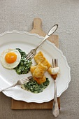 Fish fingers with creamy spinach and a fried egg
