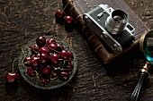 A glass bowl of sweet cherries and a camera