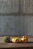 Three ornamental squashes on a wooden table