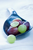 Red and green grapes on a wooden spoon