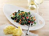 Kale Salad on a White Dish; Biscuit and Glass of White Wine