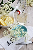 Holunderblütensaft, Zitronenscheiben und Holunderblüten auf einem bedruckten Tuch