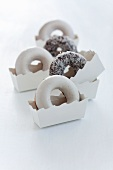 Doughnuts with sugar icing and coconut in paper cases