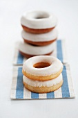 Doughnuts with sugar icing, stacked, on a striped cloth