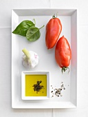 Ingredients for tomato sugo (tomatoes, garlic, olive oil, basil and spices)