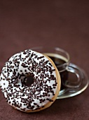 A doughnut with a sugar glaze and chocolate sprinkle and a cup of coffee