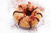 A doughnut with chocolate glaze, cocoa powder and chilli