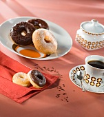 Doughnuts with sugar and chocolate glaze and a cup of coffee