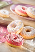 Doughnuts with a raspberry glaze, icing sugar and sugar