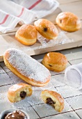 Freshly baked chocolate-filled doughnuts dusted with icing sugar