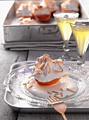A baked apricot with meringue and slivered almonds