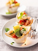 Pastry dishes filled with prawns, tomatoes, mozzarella and basil