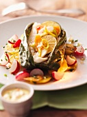Halibut in a banana leaf on a bed of potato and radish salad