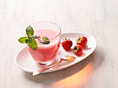 A strawberry shake with a sprig of mint